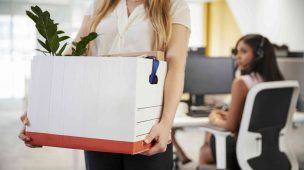 mulher carregando uma caixa com suas coisas após demissão da empresa
