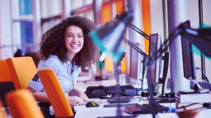 jovem mulher sorrindo na mesa de trabalho - mulheres no mercado de trabalho