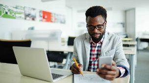 homem negro trabalhando com celular em uma mão, lápis na outra mão fazendo anotações em um caderno e com o notebook aberto - gestão do tempo e produtividade no trabalho