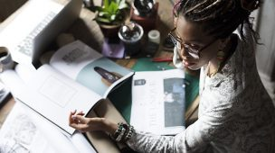 mulher negra trabalhando com a mesa cheia de coisas - ferramentas para aumentar minha produtividade