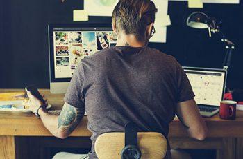 homem de costas sentado na frente da mesa do computador trabalhando home office - como ter flexibilidade no trabalho
